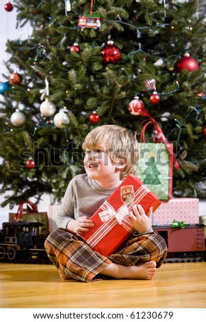 Little 4 year old boy by Christmas tree holding present
