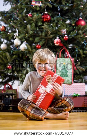 Little 4 year old boy by Christmas tree holding present - stock photo