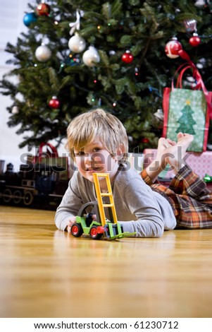 Little 4 year old boy playing with toy by Christmas tree