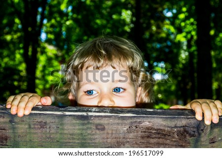 Little 3 year old girl peek over the wooden bars. - stock photo