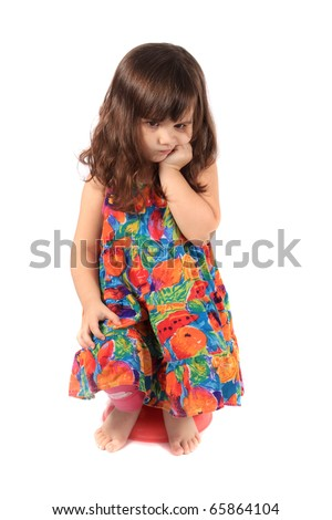 Little 3 year old girl sitting on a small stool holding her hand to her face with a sad or upset look on a white background - stock photo