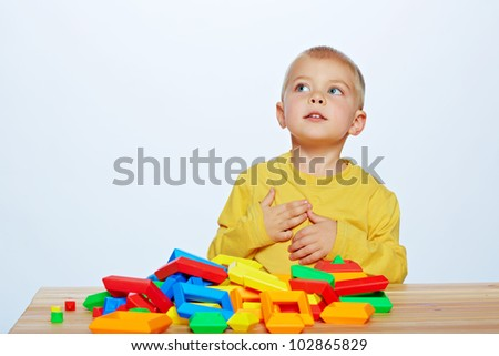 little 3 year old toddler boy playing with bright plastic pyramid blocks over light studio background - stock photo