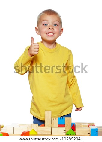 little 3 year old toddler boy playing with bright wooden blocks on a wooden table over white background - stock photo