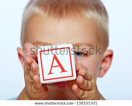 little 3 year old toddler boy playing with wooden abc alphabet blocks on studio background  - stock photo