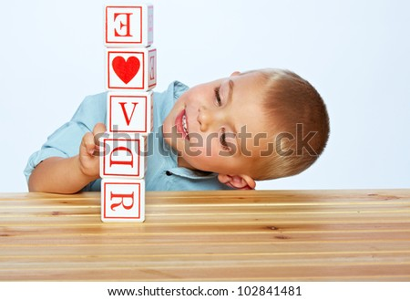 little 3 year old toddler boy playing with wooden abc alphabet blocks on the light blue studio background - stock photo
