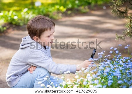 Little 7 years boy looking on the blue flowers through magnifying glass - stock photo