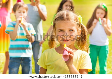Little 5 years girl on birthday party holding noisemaker horn, smile and having her friends on background