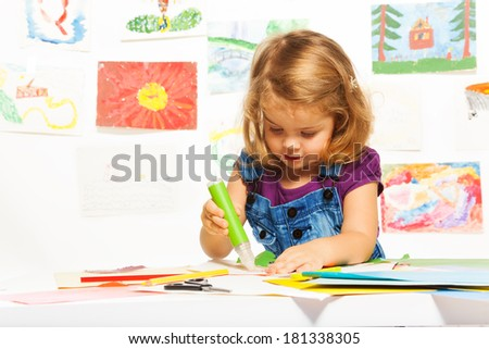 Little 3 years old blond girl gluing color cardboard with glue stick - stock photo