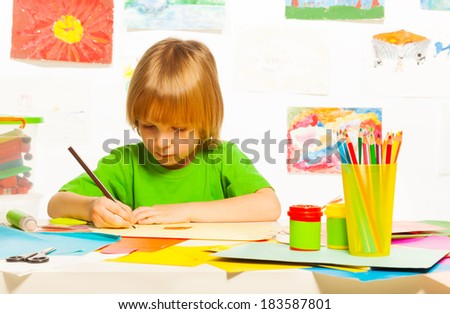 Little 4 years old boy drawing with pencil on the art class  - stock photo