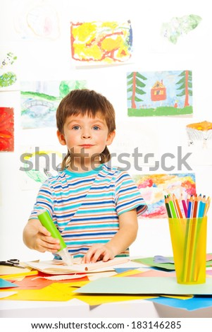 Little 3 years old boy with glue stick and pencils in the art developmental class - stock photo