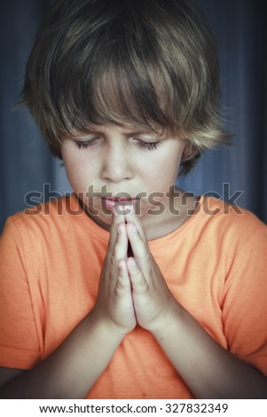 Little young beautiful boy spiritual peaceful praying and wishing - stock photo