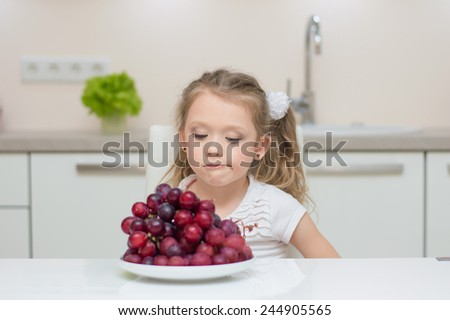 Little young beautiful cute sweet pretty girl portrait in the kitchen. Child refuse to eat healthy fresh grapes - stock photo