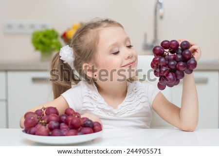 Little young beautiful cute sweet pretty happy girl portrait with dish of fresh grapes in the kitchen.  - stock photo