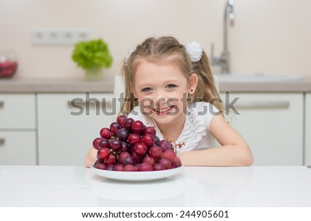 Little young beautiful cute sweet pretty happy girl portrait with dish of fresh grapes in the kitchen.