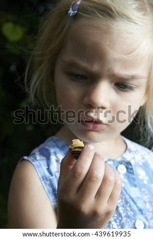 little young beautiful girl holding small snail in hand