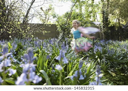 Little young blurred girl in fairy costume running in flower garden - stock photo
