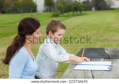 Little young boy in white shirt and his happy mother write or draw with a pencil on a sheet of paper on wood table in the park  - stock photo