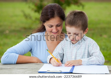 little young boy in white shirt with his mom woman teacher, writing or drawing with a pencil on a sheet of paper on wood table in the park  - stock photo
