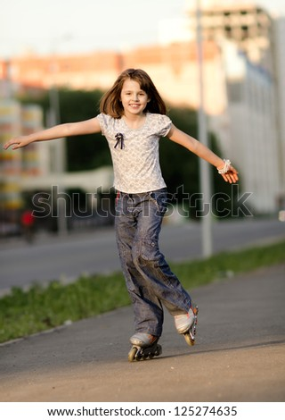 little young girl go on  roller skates, outdoor, in the evening summer - stock photo