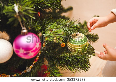 Little young girl hands decorating christmas tree with balls and other christmas toys with her family. Pre-celebration photo of New Year or Christmas. Side view unrecognizable with no face - stock photo