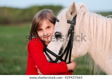 Little young girl in a red dress hugging his head a white horse Outdoors - stock photo