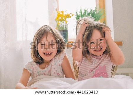 Littlegirl in bed. attractive young girls laugh. two girls dressed in pajamas lying in white bed and laughing. - stock photo