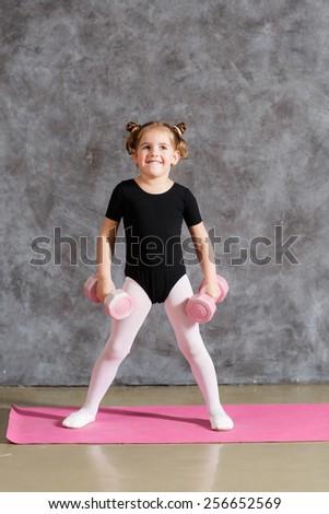 Littlte smiling girl doing exercises with dumbbells - stock photo