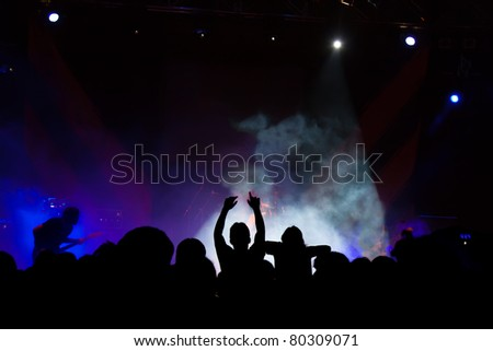 Live and powerful concert. Dark shot aiming the stage and the silhouettes of the public. The lights are delivered overexposed. - stock photo