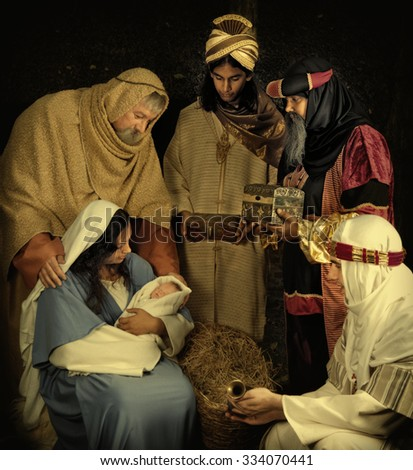 Live Christmas nativity scene reenacted in a medieval barn - the baby is a doll. - stock photo