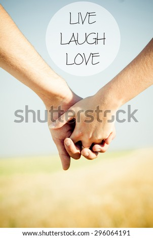 LIVE LAUGH LOVE motivational quote with close-up holding hands - stock photo
