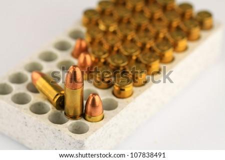 Live 9mm pistol round against white - stock photo