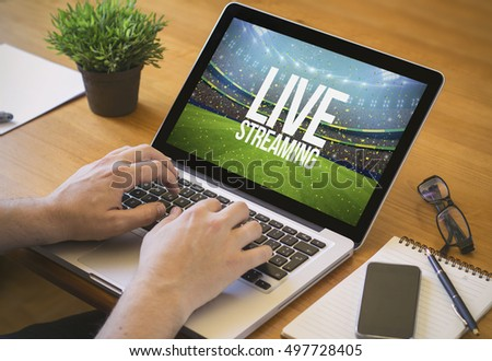 live streaming concept. Close-up top view of a man watching sports event on laptop. all screen graphics are made up.