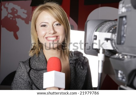 live TV transmission with a smiling  reporter in front of the video camera - stock photo