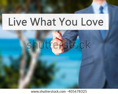 Live What You Love - Businessman hand holding sign. Business, technology, internet concept. Stock Photo - stock photo