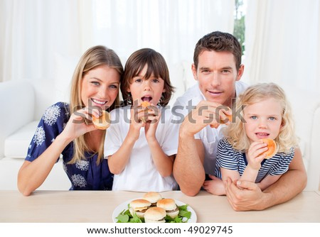 Lively family eating burgers in the living room at home - stock photo