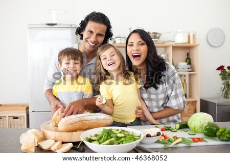 Lively family preparing lunch together in the kitchen - stock photo