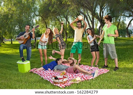 Lively group of teenagers in the park singing and dancing along to guitar music played by one of the boys as they enjoy a picnic outdoors - stock photo