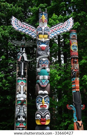 Lively historic totem poles by ancient native indian americans in the stanley park, Vancouver, British Columbia, Canada - stock photo