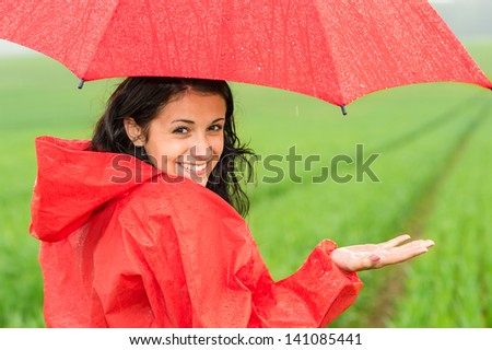 Lively teenager girl in the rain looking at camera - stock photo