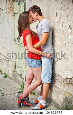 Lively young couple kissing on the street - stock photo