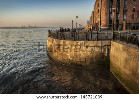 Liverpool's Albert Dock sandstone and brick warhouses bathed in late evening sunlight.