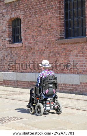 LIVERPOOL, UK - JUNE 30, 2015: Wheelchair bound visitor to the Maritime Museum, Liverpool.The Merseyside Maritime Museum is based in the city of Liverpool, and is part of National Museums Liverpool - stock photo