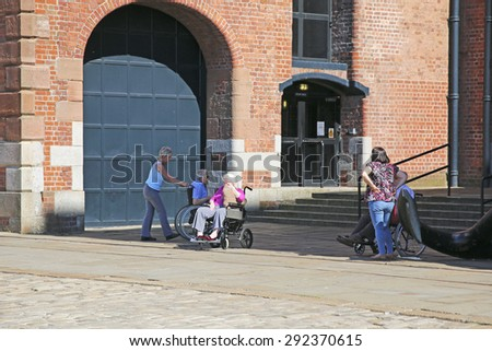 LIVERPOOL, UK - JUNE 30, 2015: Wheelchair bound visitors and their carers to the Maritime Museum, Liverpool. Liverpool is a city in Merseyside, England, on the eastern side of the Mersey Estuary - stock photo