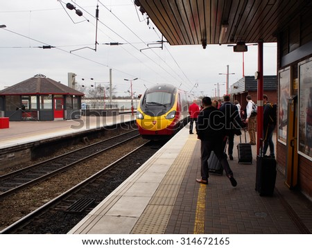 LIVERPOOL, UNITED KINGDOM - APRIL 13, 2015: people wait for high speed train at a train station in Liverpool, UK. There were 1.65 billion journeys on the United Kingdom National Rail network in 2014.