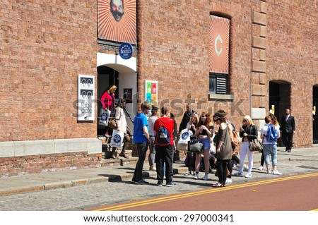 LIVERPOOL, UNITED KINGDOM - JUNE 11, 2015 - Tourists standing outside The Beatles Story building at Albert Dock, Liverpool, Merseyside, England, UK, Western Europe, June 11, 2015. - stock photo