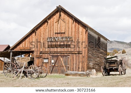 Livery, Feed and Grain, and wagons in the Montana ghost town of Nevada City. - stock photo