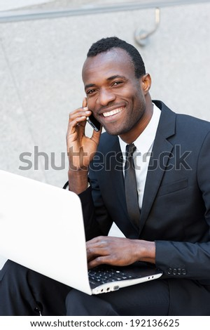 Living a business life. Cheerful young African man in formal wear talking on the mobile phone and working on laptop while sitting outdoors