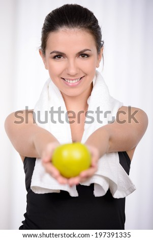 Living a healthy life. Beautiful woman in sports clothing throwing an apple up and smiling - stock photo