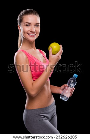 Living a healthy life. Happy young woman holding apple and bottle with water while standing against black background - stock photo