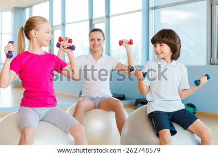 Living a healthy life. Mother and two children exercising in health club and smiling  - stock photo